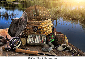 Traditional fly-fishing rod with equipment in late afternoon...