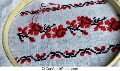 Traditional folk embroidery cross on a wooden hoop