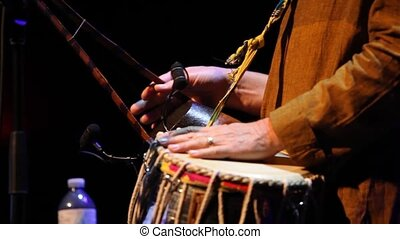 Close up shots of a musician playing a table, a vintage drum originating from India and commonly used in folk music.