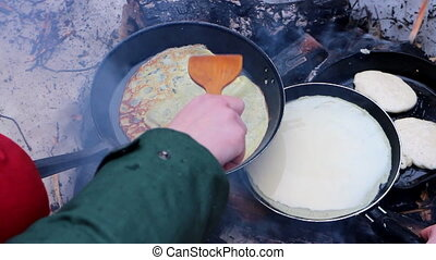 Traditional food 2. Russian cuisune: pancakes over an open...