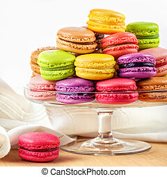 traditional french colorful macarons in a glass cake stand on wooden table