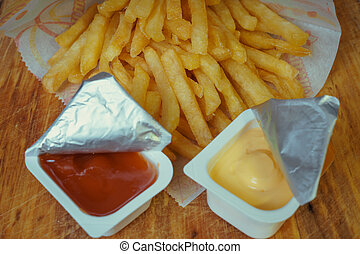 Traditional french fries in a package with ketchup and mustard on a wooden board