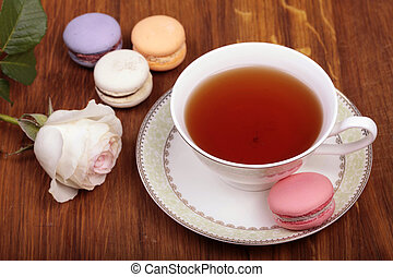 traditional french macrons with tea set on wood background,...
