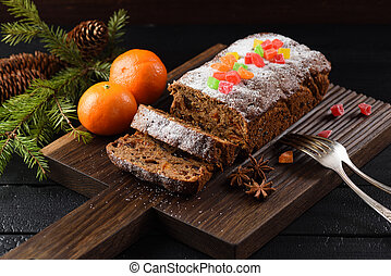 Traditional fruit cake for Christmas served on wooden board with clementines on black background