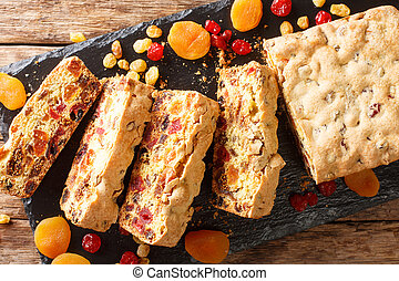 Traditional fruit cake with dried apricots berries raisins figs cherries closeup on a slate board. horizontal top view