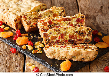 Traditional fruit cake with dried apricots berries raisins figs cherries closeup on a slate board. horizontal