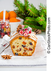 Traditional fruit cake with mixed fruit and cherries decorated with sugar icing, cranberries, pomegranate and cherry on a white background. Vertical orientation.