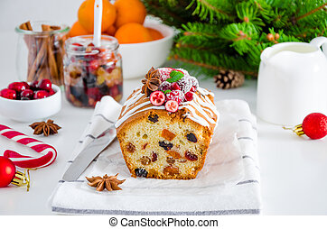 Traditional fruit cake with mixed fruit and cherries decorated with sugar icing, cranberries, pomegranate and cherry on a white background. Horizontal orientation.