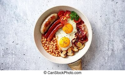 British Full English Breakfast including sausages, grilled tomatoes, mushrooms, eggs, bacon, baked beans and bread. Top view.