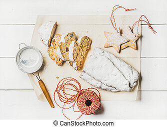 Traditional German Christmas cake Stollen cut in pieces, cookies, rope