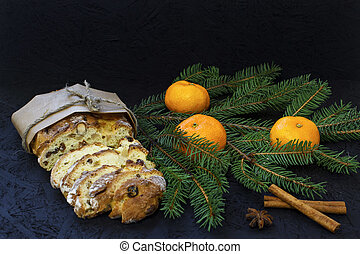 Traditional German Christmas pastry - stollen on a black background with fir branches, spices and Christmas decorations