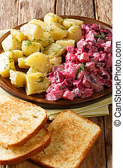 Traditional German red herring salad with garnish of boiled potatoes close-up in a plate. vertical