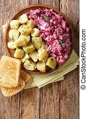 Traditional German red herring salad with garnish of boiled potatoes close-up in a plate. Vertical top view