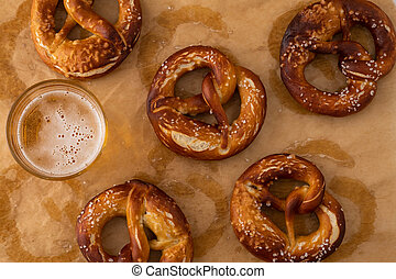 Traditional German Savory Lye Pretzel with Salt on Piece of Parchment Paper. Poster Banner for Bakery. Copy Space.Top View.Toned image.
