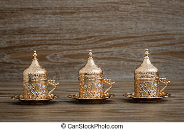Traditional Golden Coffee Cup Set in a Tray on Wooden Background