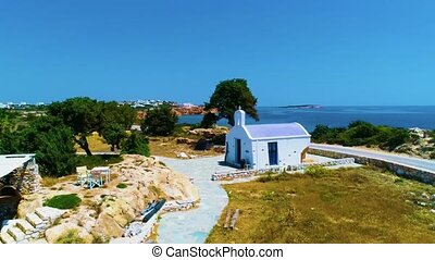 Traditional greek church with island and sea on background