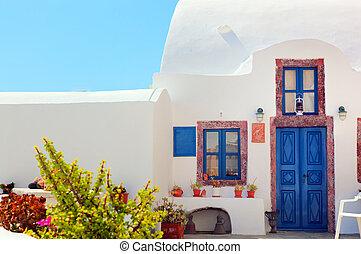Traditional Greek house with blue door and windows, Santorini, Greece.