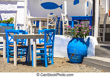 Traditional Greek tavern in the beach side with typical blue chairs. Astypalea island, Greece