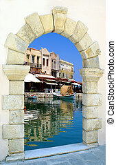 Traditional harbor through an old door in Crete island, Greece