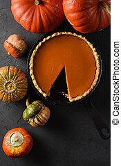 Traditional homemade pumpkin pie and bright squashes on black background top view copy space. Low key still life with natural lighting
