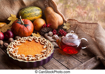 Traditional homemade pumpkin tart pie healthy sweet dessert recipe with tea. Halloween or thanksgiving holiday celebration meal. Autumn composition decoration and natural light. Vintage wooden background.