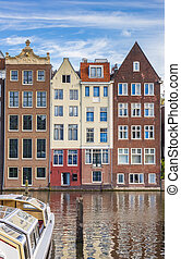 Traditional houses and a cruiseboat at the Damrak in Amsterdam