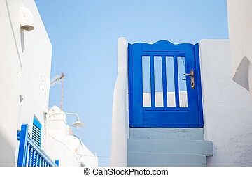 Traditional houses with blue door and white stairs in the narrow streets of Mykonos, Greece.