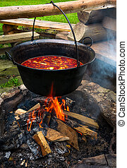 traditional Hungarian Goulash soup in cauldron. meal cooked...