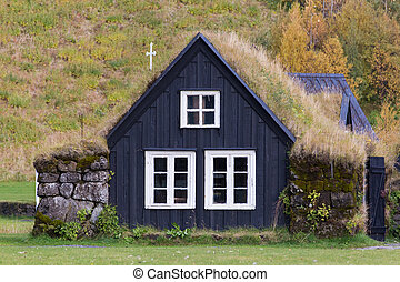 Traditional Icelandic House with grass roof. Skogar Folk...