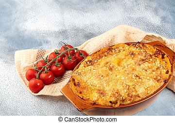 Traditional italian canelonni with vegetables, minced meat and cheese. On a wooden background. Top view, copy space