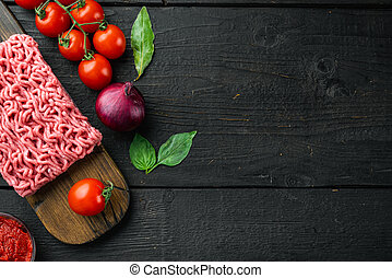 Traditional italian tomato sauce bolognese with ingredients, minced meat tomatoe and herbs, on wooden cutting board, on black wooden table background, top view, flat lay, with copy space for text