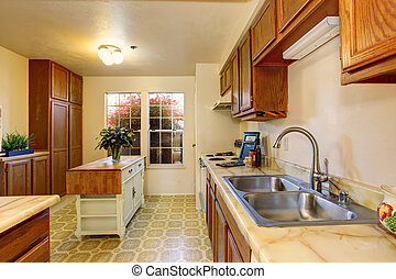 Traditional kitchen with tile floor, and small island.