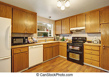 traditional kitchen with wood floor and cabinets.