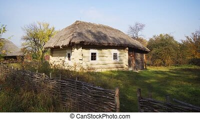 Traditional log cabin with thatched roof at an educational cultural village, at a rural site in Ukraine.