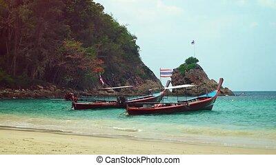 Handmade longtail boats, flying the Thai national flag, tied along a tropical beach near Phuket, Thailand, on a cloudy day. Video 4k