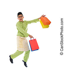 Traditional Malay male shopping and jumping in joy during hari raya ramadan festival