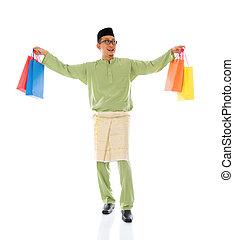 Traditional Malay male shopping and jumping in joy during hari raya ramadan aidilfitri festival