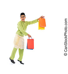 Traditional Malay male shopping and jumping in joy during hari raya ramadan festival