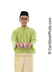 Traditional Malay male with biscuit during hari raya