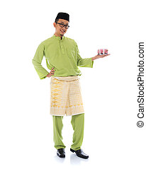 traditional malay male with raya cookie
