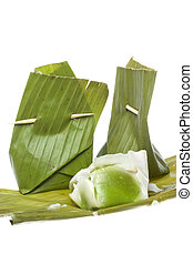 Isolated macro image of traditional Malay pastries (kuih) wrapped in screwpine (pandan) leaf.