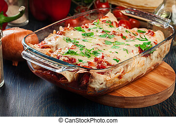 Traditional mexican enchiladas with chicken meat, spicy tomato sauce and cheese in heat resistant dish
