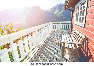 bench for rest at the norwegian terrace house with mountains and a waterfall in the background, norway