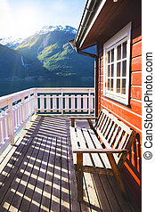 benches for rest at the norwegian terrace house with mountains and a waterfall in the background, norway