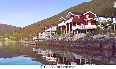rorbuer - traditional norwegian red wooden house to stand at the lakeside and mountains in the distance, norway