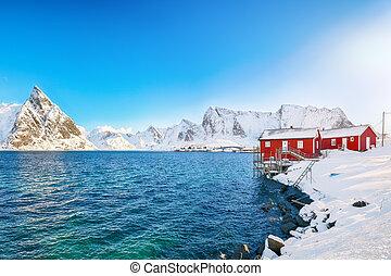 Traditional Norwegian red wooden houses on the shore of  Reinefjorden on Toppoya island