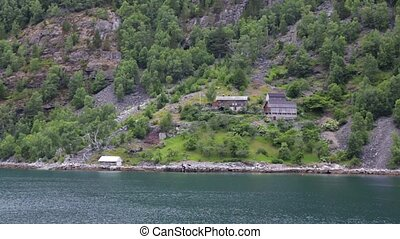 Traditional Norwegian village houses near the sea with green...