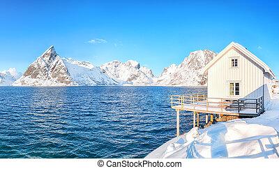 Traditional Norwegian wooden houses on the shore of  Reinefjorden on Toppoya island