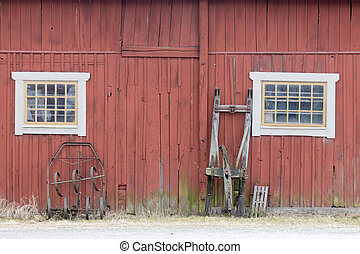 Traditional old red barn wall, a window and a sled