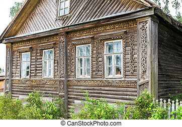 Traditional old Russian wooden house with carved wooden trim in Novgorod region, Russia